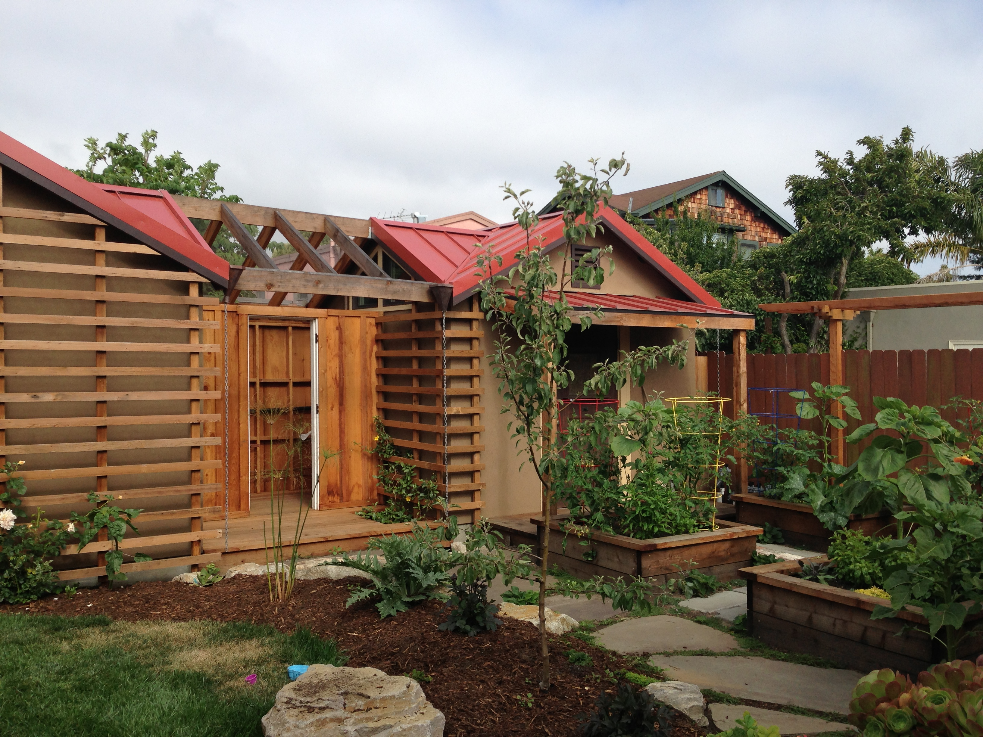 trellises, vegetable beds, and roses and vines starting to climb