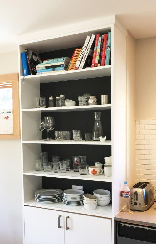 Tall Shelving Between Kitchen and Dining Area for All the Dishes